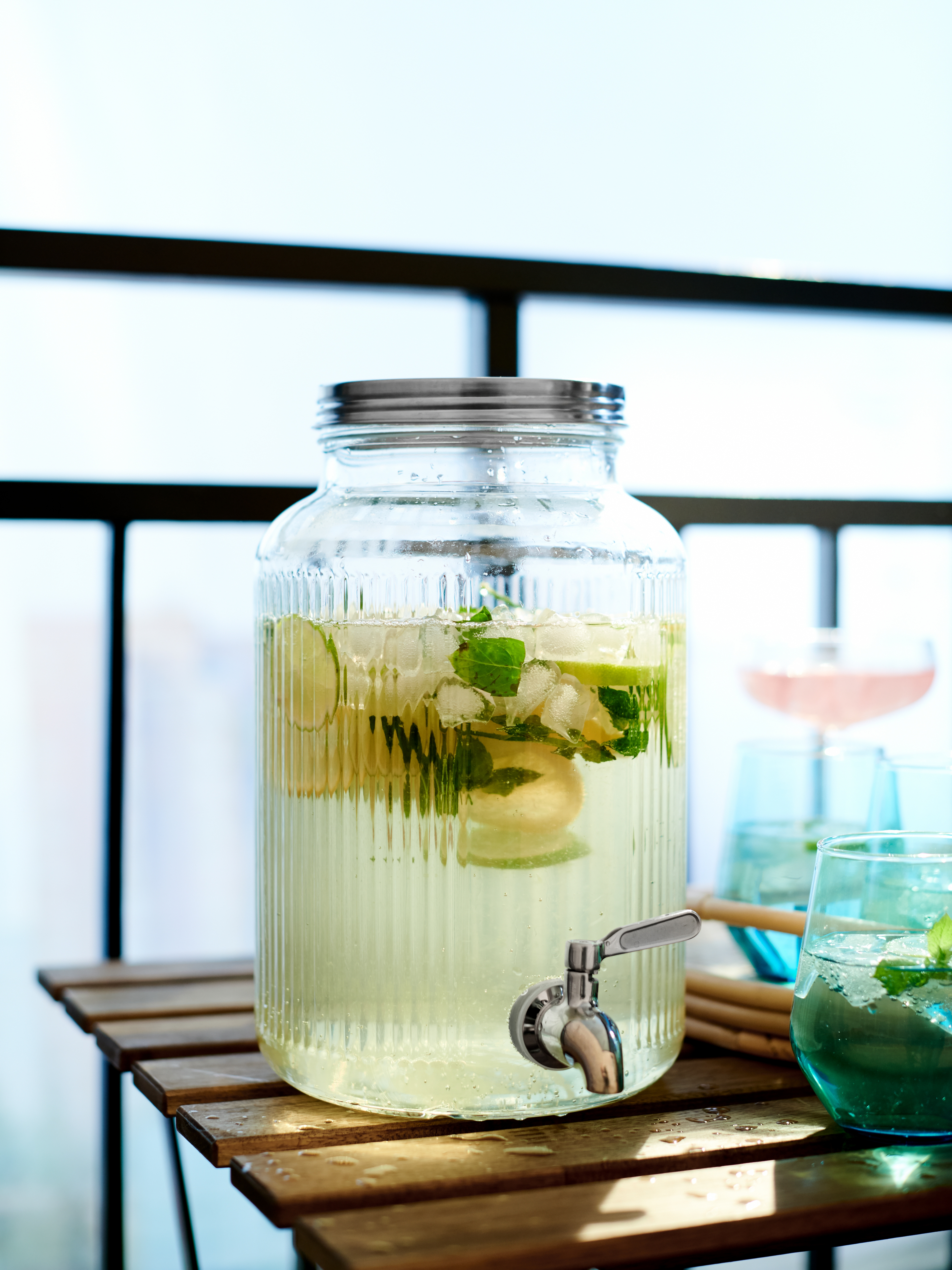 This 5 litre VARDAGEN glass jar with lid and tap holds a citrus drink. It's ready to pour drinks on a balcony table.