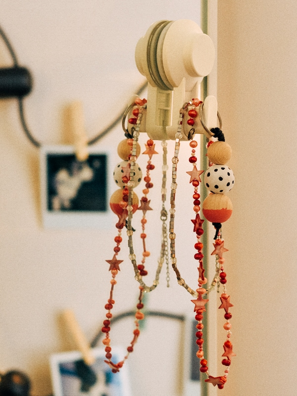 A close-up of a chunky wooden necklace hanging on a TISKEN hook put on a mirror using the suction cup.