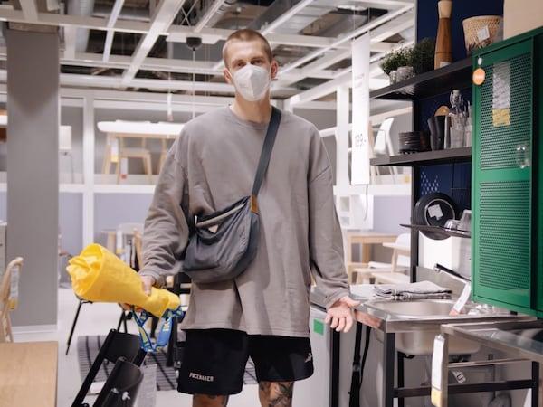 A közösségi média sztárja, Willy Iffland egy IKEA áruházban, hosszú ujjú szürke pólóban és fekete rövidnadrágban.