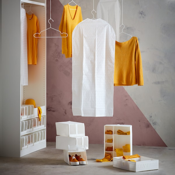 White SKUBB organizers and shoeboxes and yellow garments on hangers artfully arranged in and next to a doorless PAX wardrobe.