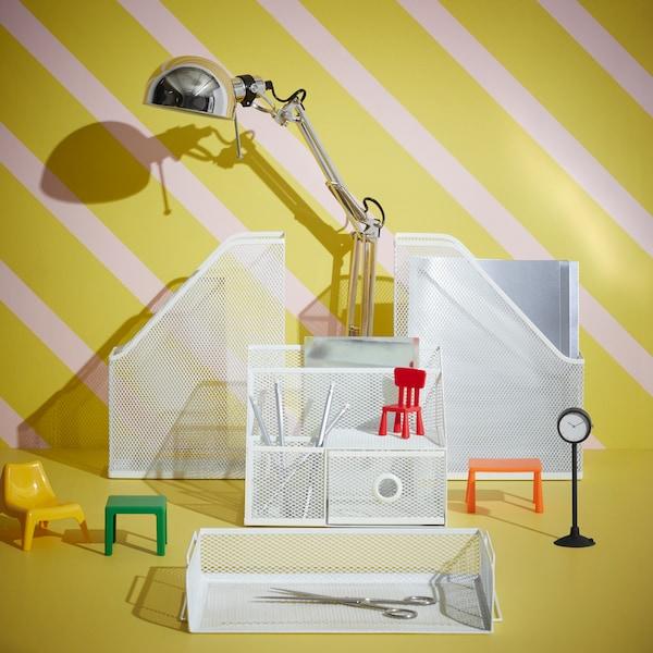 Na beli mizi je kovinski pisemski odlagalnik s tremi nivoji, na katerem so plastične posode, mape in različni predmeti.