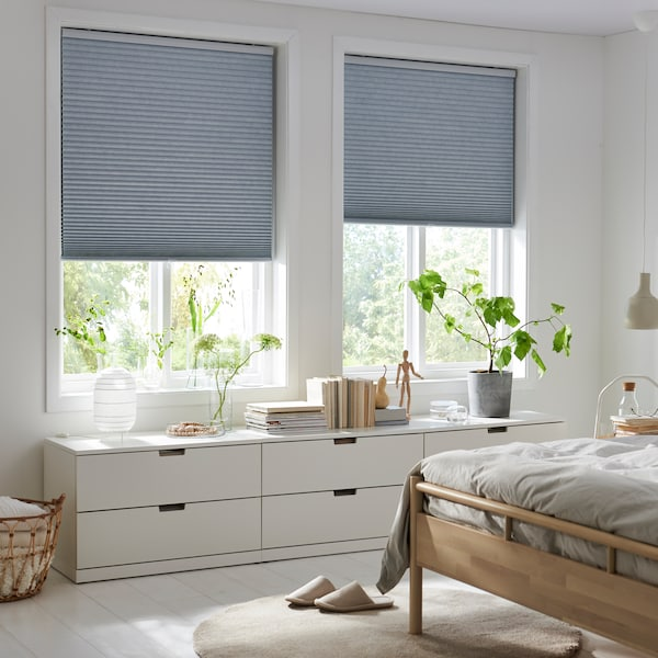 Two windows with TRIPPEVALS cellular blinds half down, BJÖRKNÄS bed frame and NORDLI chest of drawers in a light bedroom