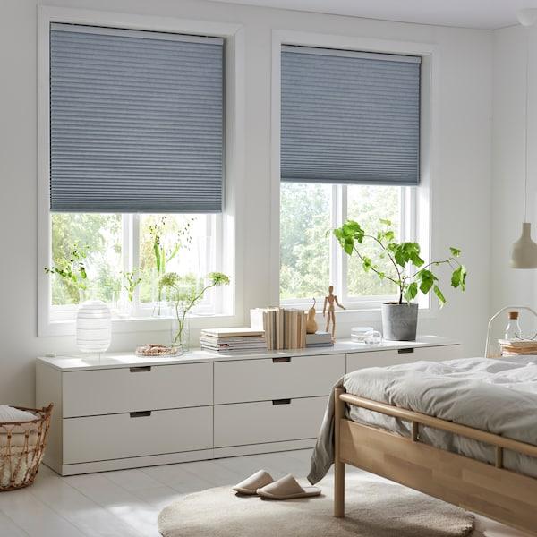Deux fenêtres garnies de stores alvéolaires TRIPPEVALS à demi abaissés, lit BJÖRKNÄS et commode NORDLI dans une chambre à coucher décorée dans des teintes claires.