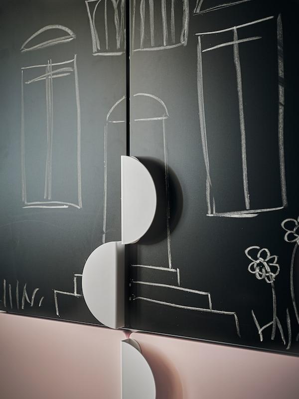 Kaksi SMÅSTAD-vaatekaapin ovea, joissa on liitutaulupinta ja BEGRIPA-vetimet.