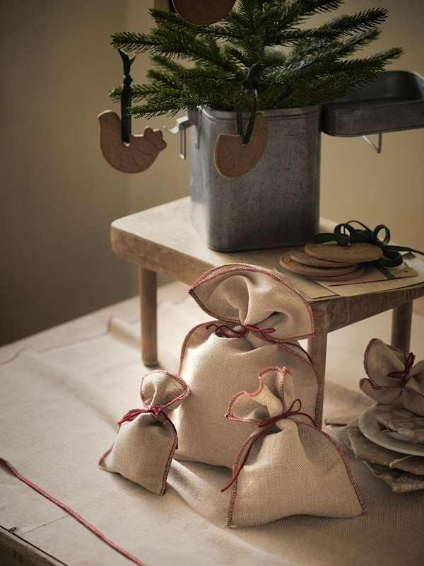 A number of gifts wrapped in VINTER 2020 jute gift wrap underneath a small pine tree with wooden hanging animals on it.