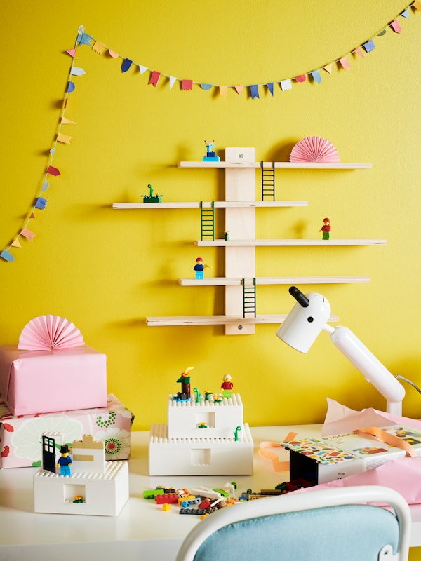 Children toys BYGGLEK on a white table with KRUX table lamp and LUSTIGT on the wall.