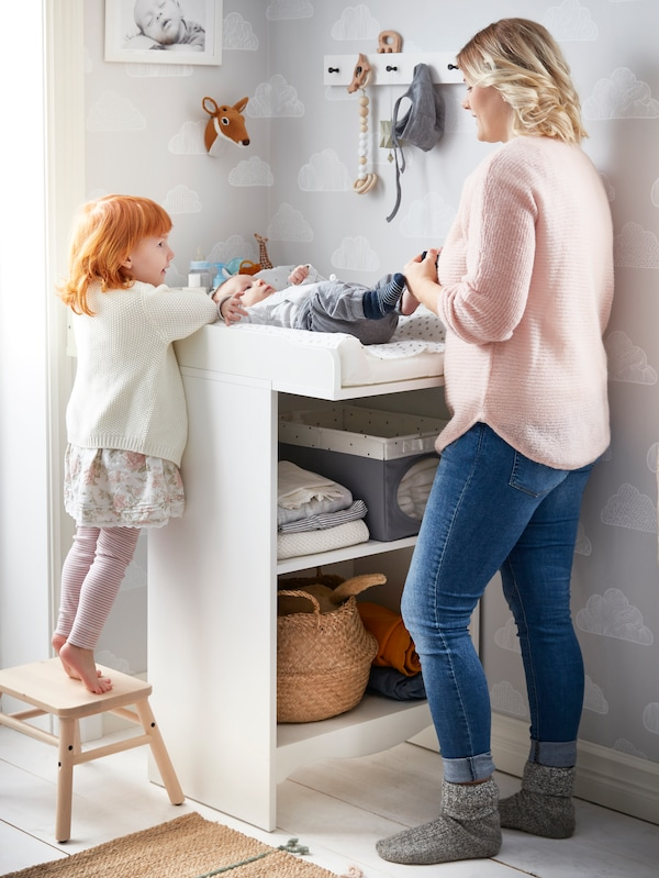 A SMÅGÖRA changing table with a baby lying on it being changed by its mother. A girl is standing on a step stool looking on.