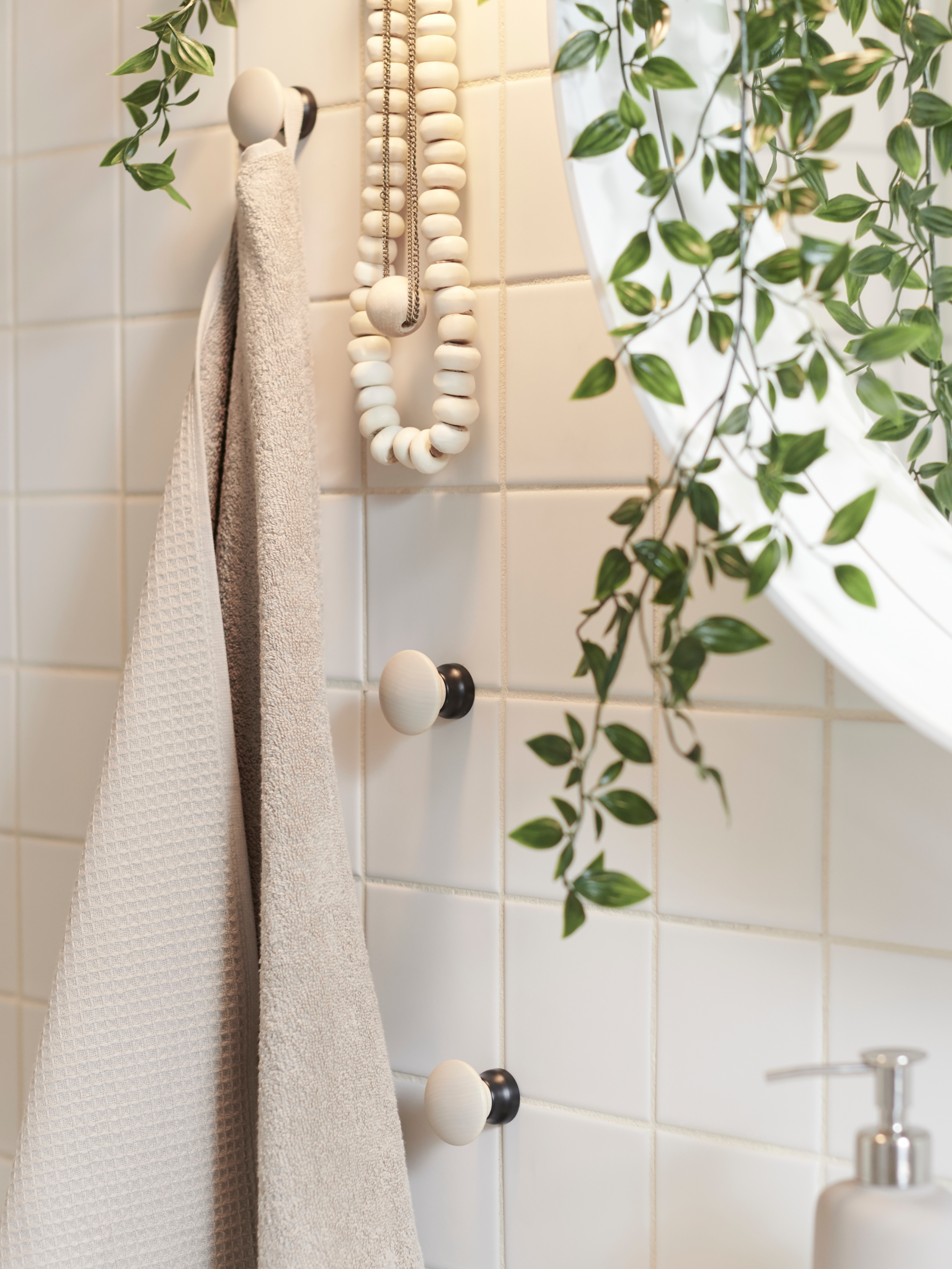 A beige SALVIKEN bath towel and necklaces hanging beside a mirror on LILLASJÖN knobs in a bathroom with white tiles.