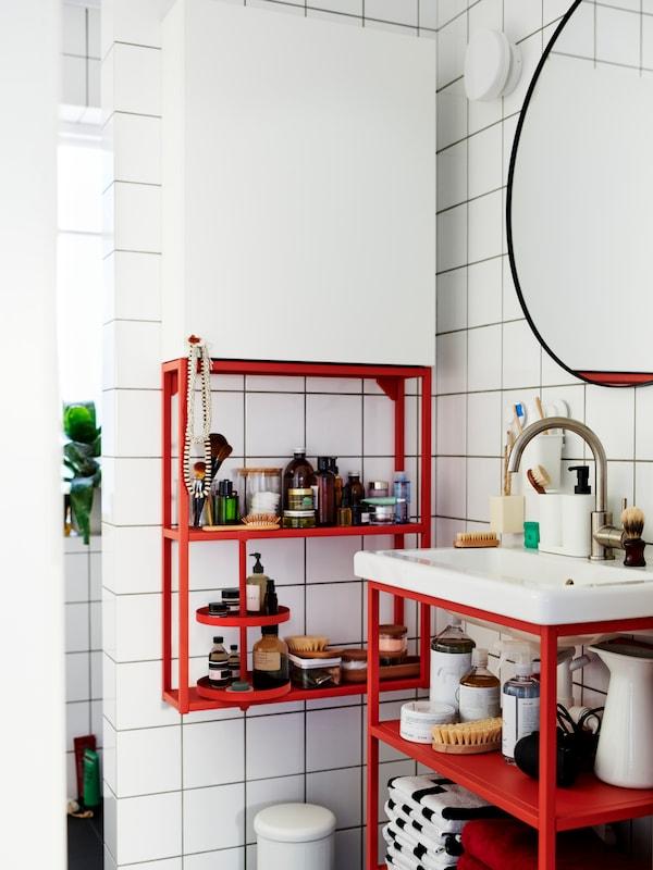 Біла навісна шафа з червоно-помаранчевим відкритим модулем та біла раковина з червоно-помаранчевим відкритим модулем під раковину.