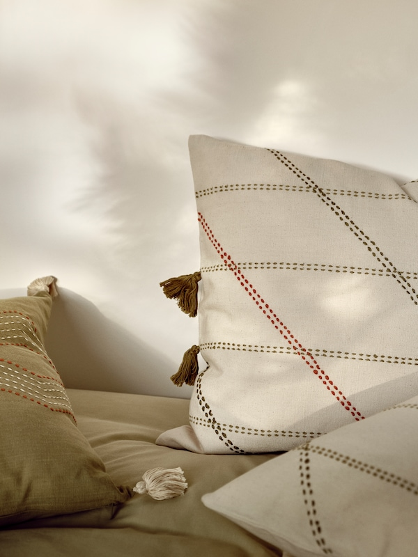 To puder med HERVOR pudebetræk og en pude med et grønt HALLVI pudebetræk på en UTÅKER seng, der kan stables.
