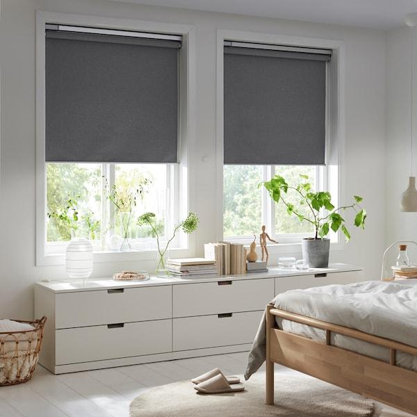 Une chambre avec de grandes fenêtres partiellement voilées par des stores intelligents IKEA gris.