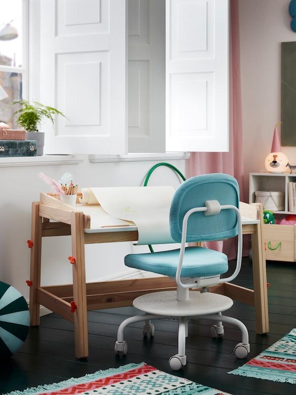 Birou pentru copii FLITSAT cu o rolă de hârtie de desen așezat lângă fereastră și un scaun turcoaz de birou pentru copii alături.