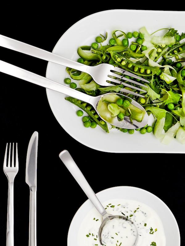 O furculiță și o lingură dintr-un set de servire pe o farfurie de servire albă ce conține verdețuri și un bol de dressing alb.
