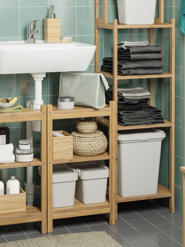 Open wooden shelving units by a wash-basin on a green tiled wall. HÅLLBAR bins with lids and other items are on the shelves.