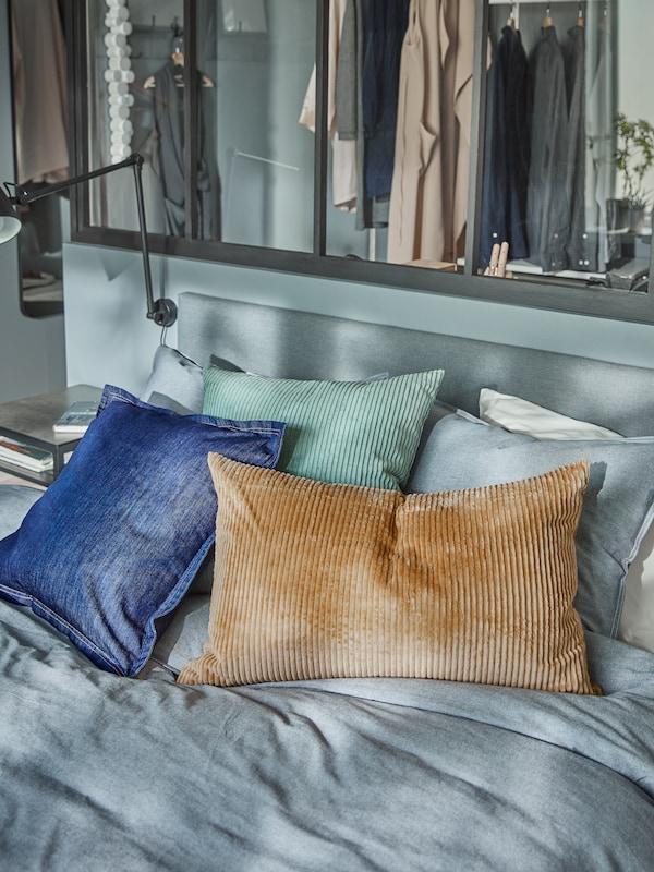 Cuscini con diverse fodere tra cui una fodera beige scuro ÅSVEIG e una fodera blu SISSIL sopra un divano letto SÄBÖVIK.