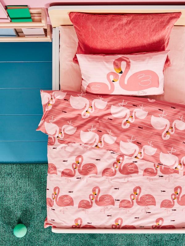 Hvidt sengestel til børn med lyserødt lagen og sengetøj med flamingoer, et grønt tæppe og en tøjbold på et blåt gulv.