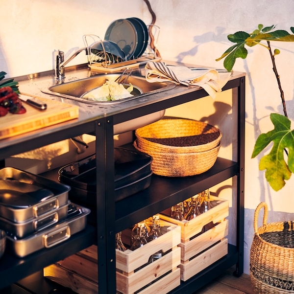 The GRILLSKÄR outdoor sink and storage units in an outdoor space with various cooking and prep supplies stored within.