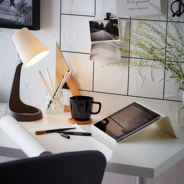 A close up image of a white desk top with a black wire notice board above with various papers and items hanging on it. The desk had a work lamp, mug, pencil cup and tablet on it.
