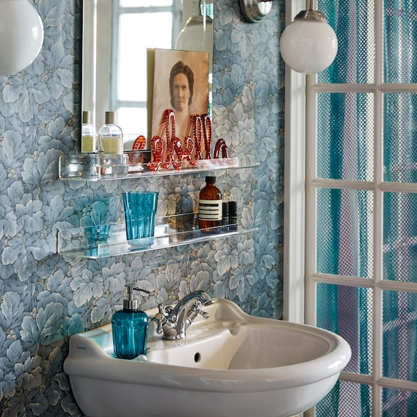 Two transparent MELLÖSA picture ledges with toiletries on them, above a washbasin in a bathroom with blue floral wallpaper.