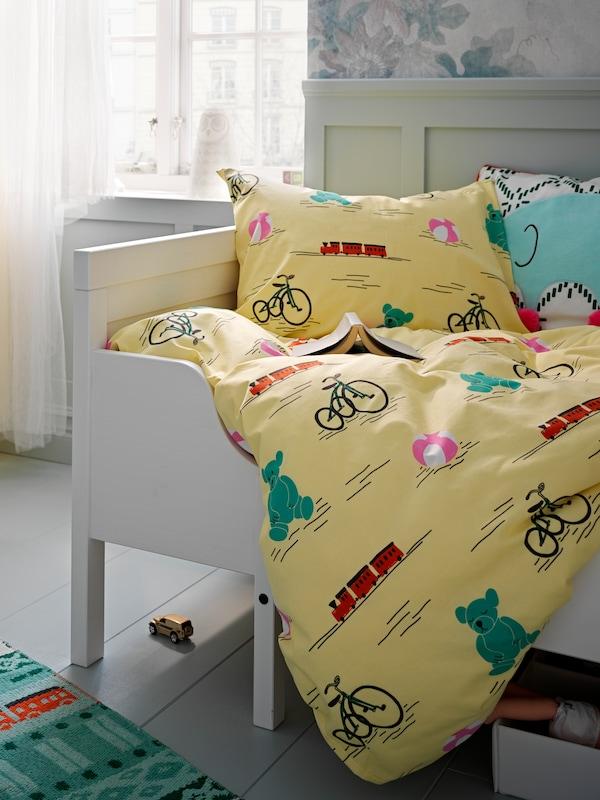 Lenjerie de pat KÄPPHÄST galbenă cu imprimeuri jucării, pe un pat alb pentru copii. Pe podea alături, un covor plin de culoare și o jucărie de pluș.