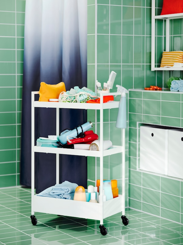 A green-tiled bathroom with a NYCKELN shower curtain and a white NISSAFORS trolley filled with towels and hair styling items.