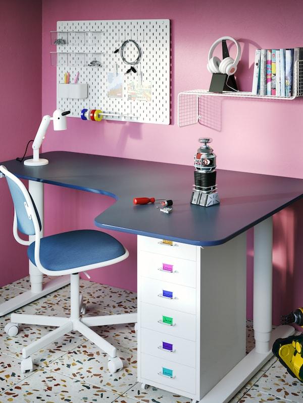 Un bureau bleu et blanc avec une chaise bleue et blanche, une lampe et d'autres objets sur le bureau, un panneau perforé et une tablette accrochés au mur.