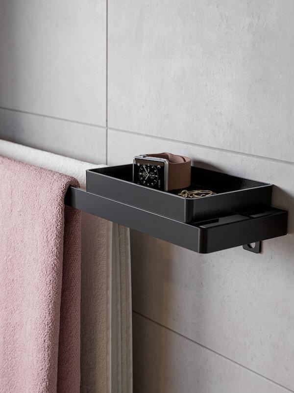 Un toalleiro negro con bandexa. No toalleiro hai dúas toallas de baño colgadas, unha branca e outra rosa claro, e na bandexa hai un reloxo.