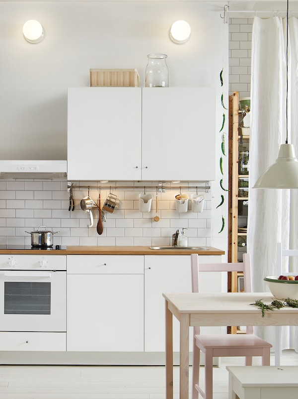 A kitchen with light-grey wall cabinets and base cabinets, a white oven, and a shelf unit storing various items.