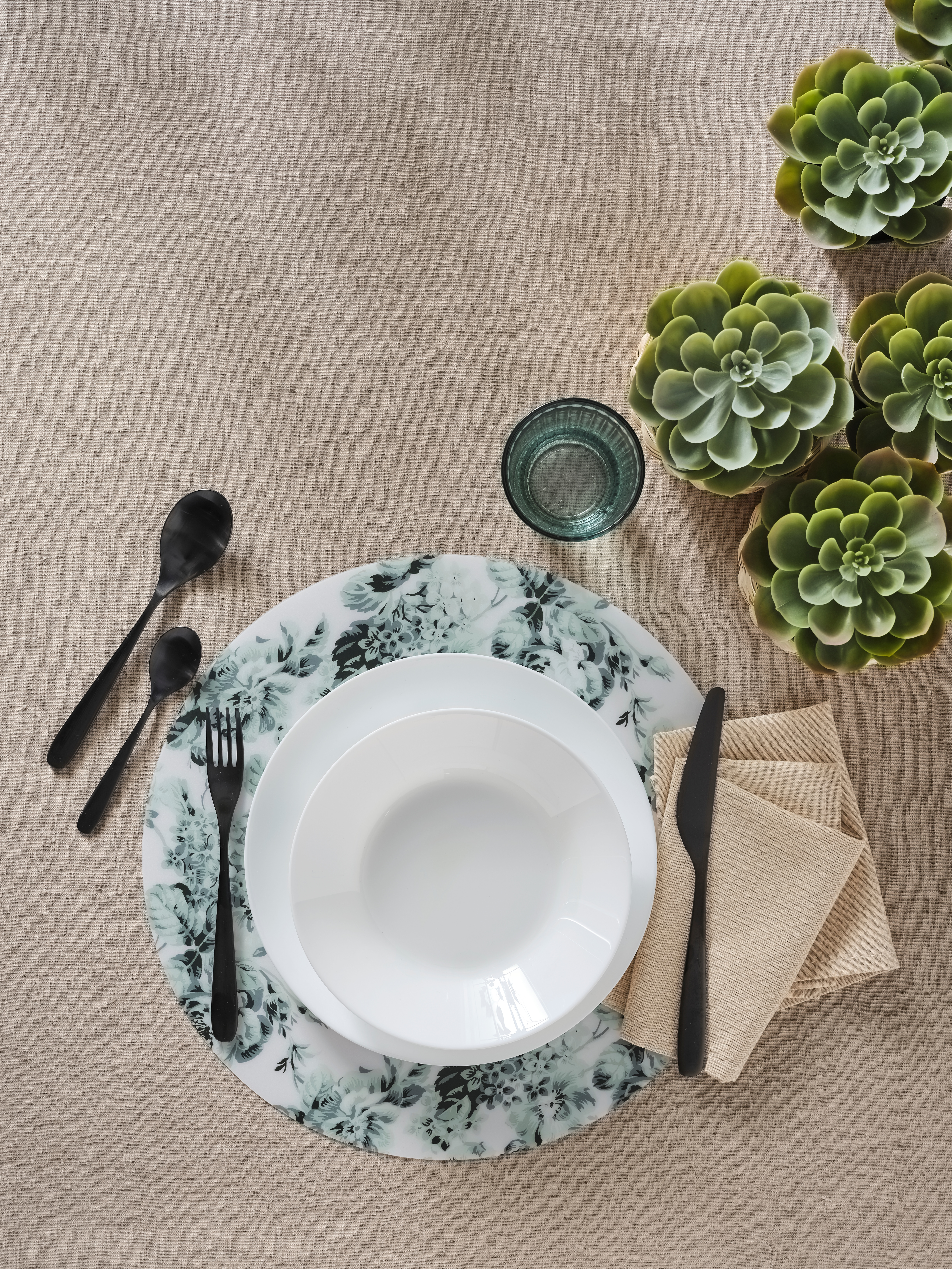 An aerial view of a white OFTAST deep plate on a larger plate and a place mat. It is by cutlery, napkins, a glass and plants.