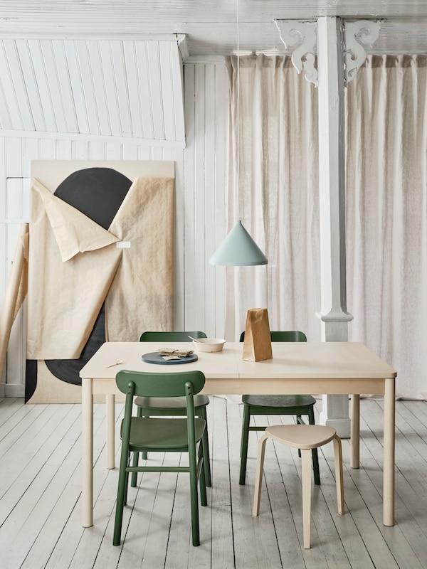 Ett RÖNNINGE utdragbart bord i björk med RÖNNINGE stolar i grönt runtom samt en KYRRE pall, även den i björk och ovanför borde hänger en NÄVLINGE taklampa i ljusblått.