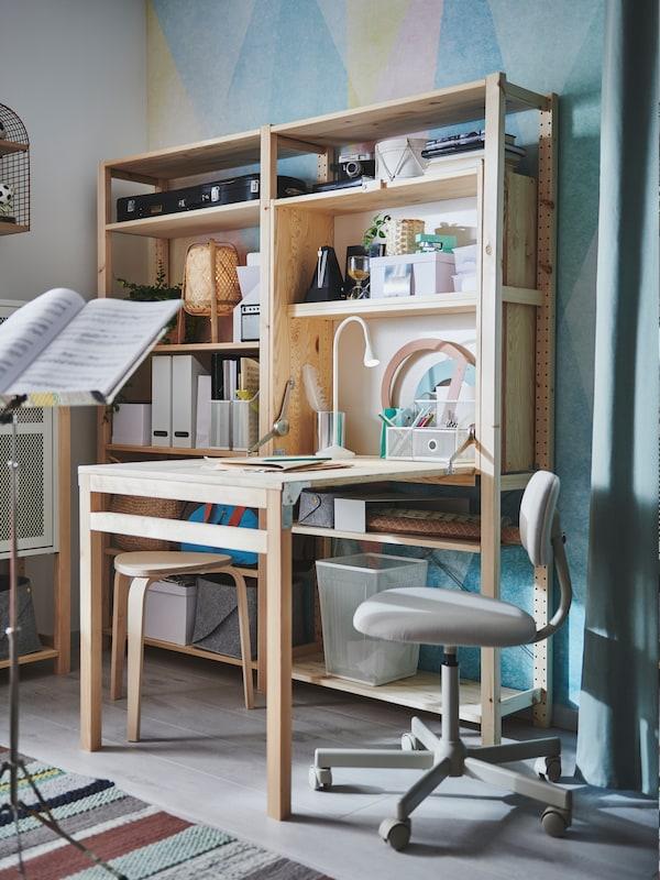 Unidade de almacenaxe IVAR de dúas seccións coa mesa despregada e unha cadeira xiratoria BLECKBERGET beixe ao carón.