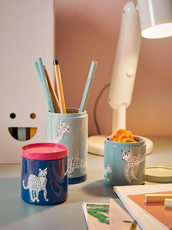 Drei Behälter in Blau und Hellgrün mit Katzenmuster sind in diesem Bild mit Stiften und Radiergummis bestückt.