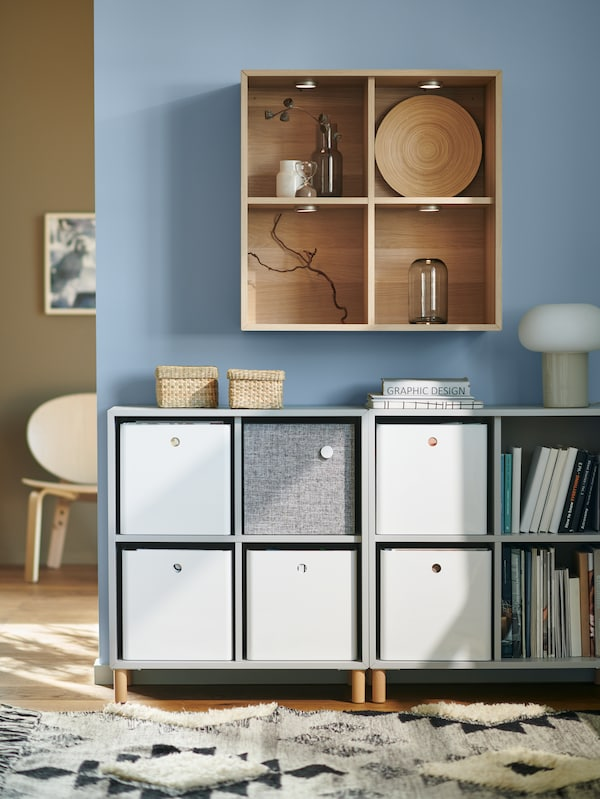 Light grey EKET cabinet combination with legs placed against a light blue wall holding white KUGGIS storage boxes and books.