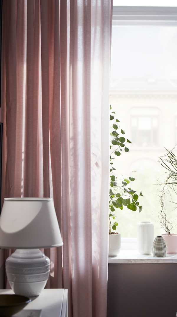 Living room windows, with HANNALILL curtains in pink filtering the light, and some plants and plant pots in the windowsill.