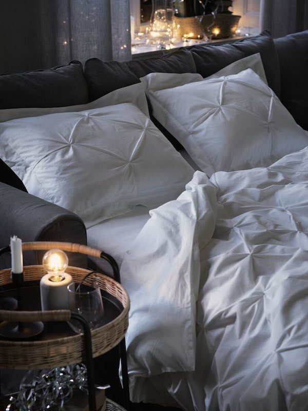 A dark grey sofa-bed made up with TRUBBTÅG bed linen at night time. A round LUBBAN trolley table with storage is by the bed.