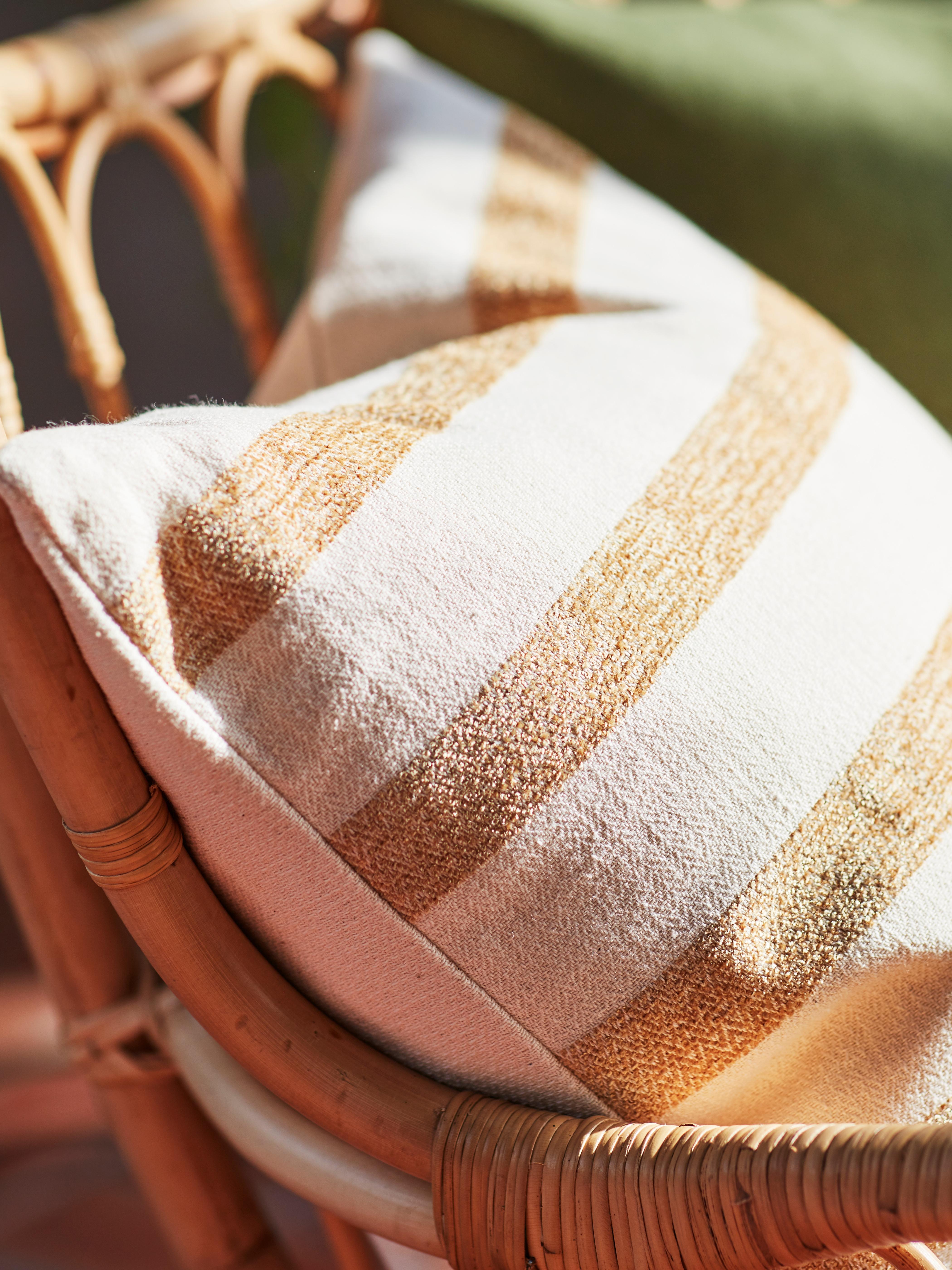 Krupni plan kuta prirodnog zlatnožutog/prugastog KNIPPARV ukrasnog jastuka, s mekanom, ali nepravilnom teksturom.