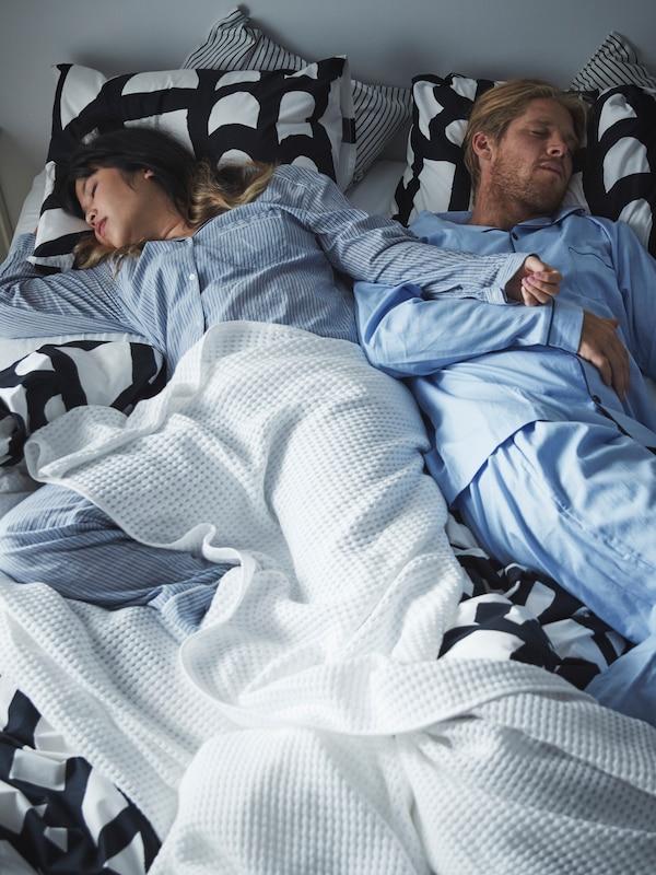 Moški in ženska spita na postelji s črno-belo SKUGGBRÄCKA posteljnino in belim VÅRELD pregrinjalom.