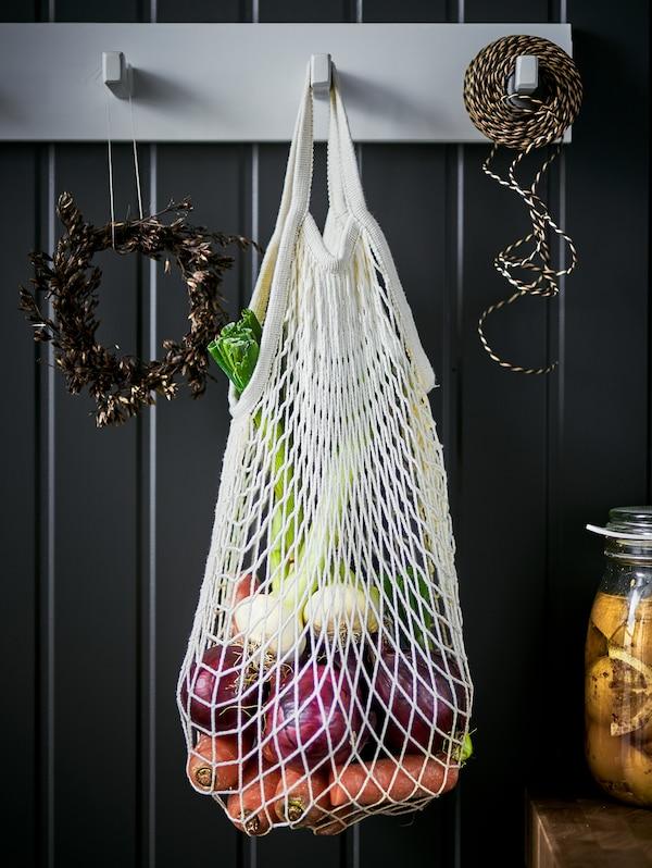 O pungă de plasă KUNGSFORS cu ceapă, morcovi și alte legume agățate pe un cârlig de perete pe un perete negru placat.