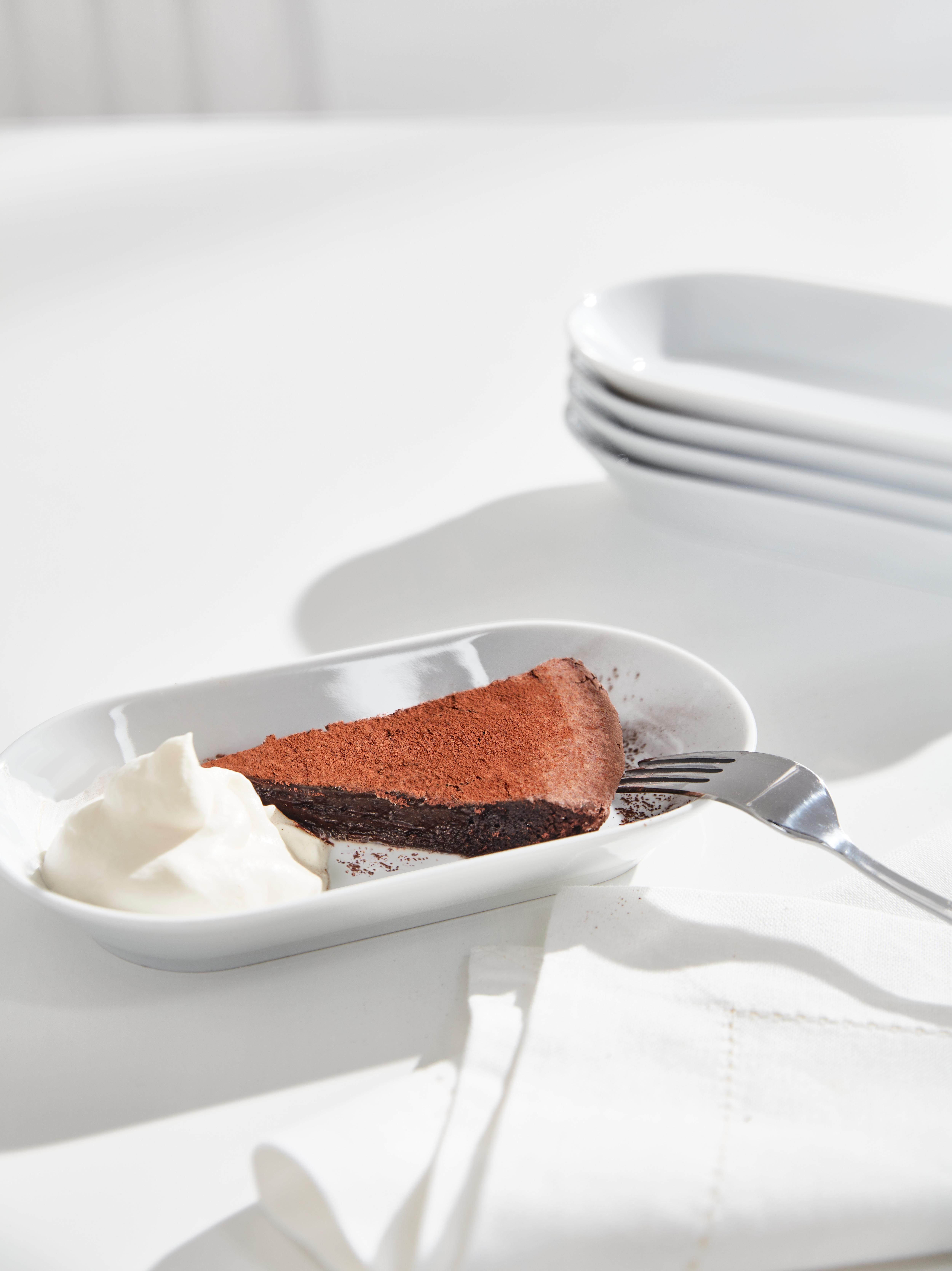 IKEA 365+ serieko feldespato zuri portzelanazko plaka obalatua, txokolate tarta zati batekin, esnegainarekin eta sardexka batekin.