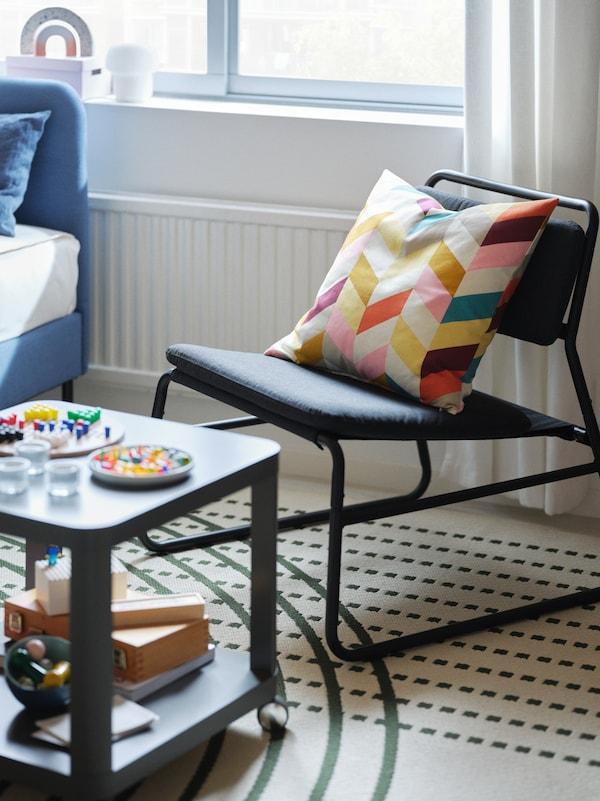 Poltrona preta com almofada colorida em cima, ao lado uma mesa de apoio. Poltrona e mesa de apoio sob um tapete TÖMMERBY