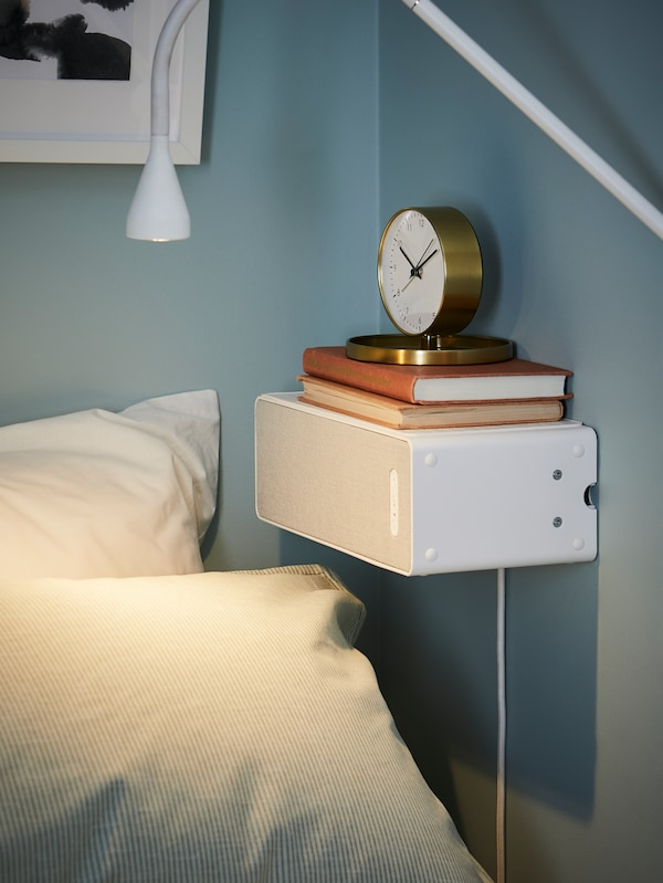 White, SYMFONISK WiFi speaker mounted horizontally on a blue wall by a bed, with two books and a gold-coloured clock on top.