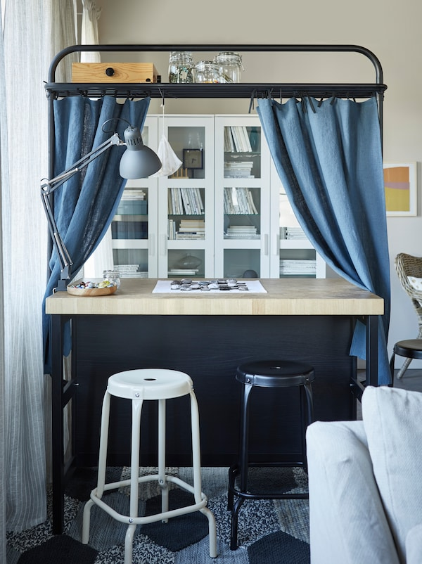 A kitchen island used as a desk in front of white glass cabinets with stools in front. Curtains hang from the frame.