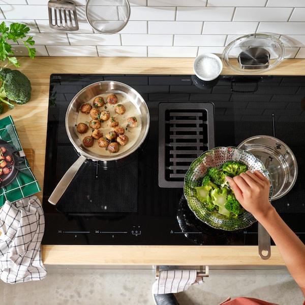 Ruka, která přidává něco do mísy se zeleninou, na varné desce vedle dvou pánví, z nichž v jedné se vaří jídlo.