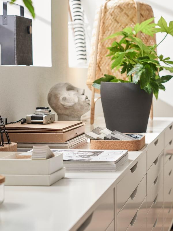 KNIXHULT bordslampa, krukväxt och olika prydnadsföremål på fyra vita ALEX hurtsar med lådor.
