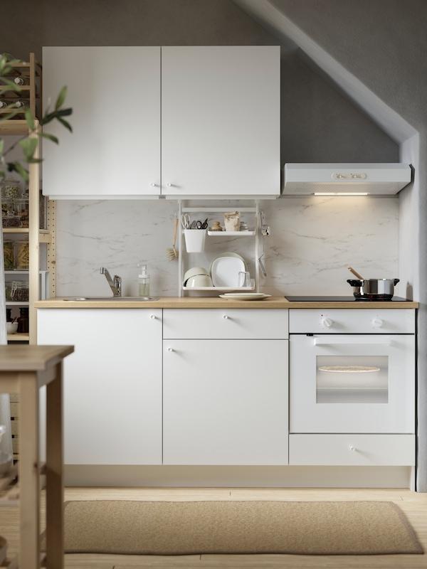 Piccola cucina bianca con mobili base e pensili bianchi, rivestimento da parete effetto marmo bianco e forno.