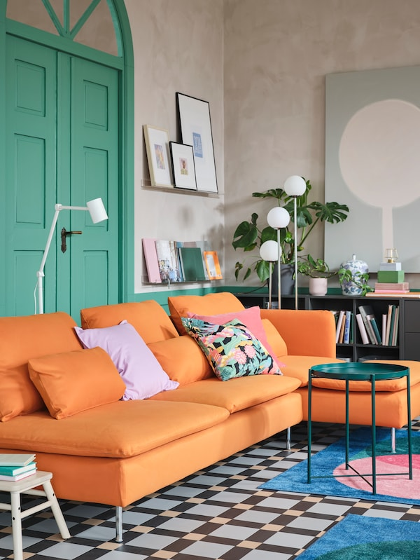 An orange 4-seat sofa with chaise longue, a dark green tray table, two bold print rugs and two white floor lamps.