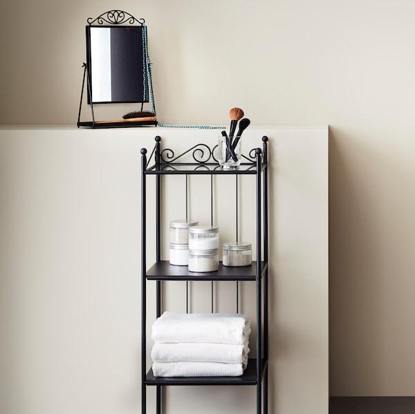 A beige bathroom with a black RÖNNSKÄR shelving unit with three white folded towels and jars of bath salt on the shelves.