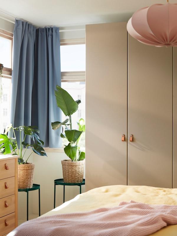Le coin d'une chambre à coucher avec une armoire-penderie PAX/REINSVOLL près de fenêtres avec des rideaux BENGTA et des plantes dans des paniers sur des tables d'appoint GLADOM.
