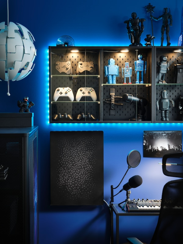UPPSPEL vitrinskåp på väggen i ett gamingrum med blå belysning, fyllt med actionfigurer och samlarföremål.