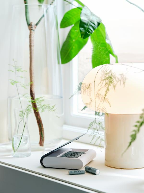 Batterioplader med opbevaring, en glasvase med en gren og en bordlampe af opalhvidt glas i en vindueskarm.